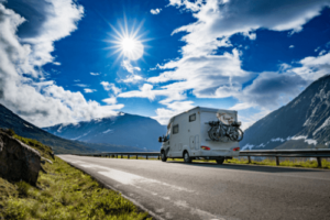 How To Prevent Tire Blowouts During Your Summer RV Trip with RV Masters in Kenner La. image of rv traveling on road with blue sunny sky and mountains on each side with bikes on back bike rack