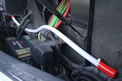 Fire Prevention By Fire Suppression Systems with RV Masters in Kenner La, image of installed fire suppression system long white tube with red caps on each end